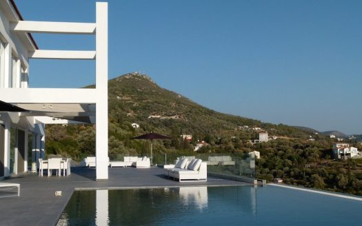 Corner on spacious terrace with infinity pool, lounge area and great view of Samos